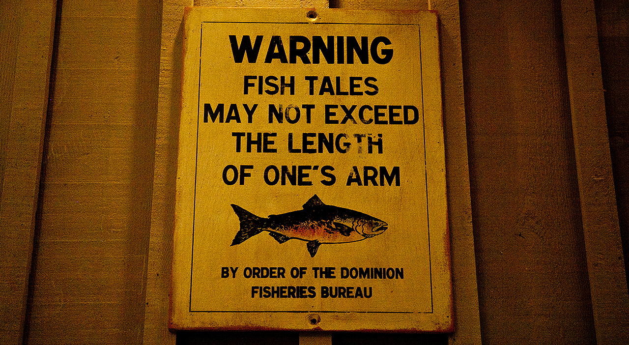 Sign that reads: WARNING fish tales may not exceed the length of one's arm. By order of the dominion fisheries bureau.